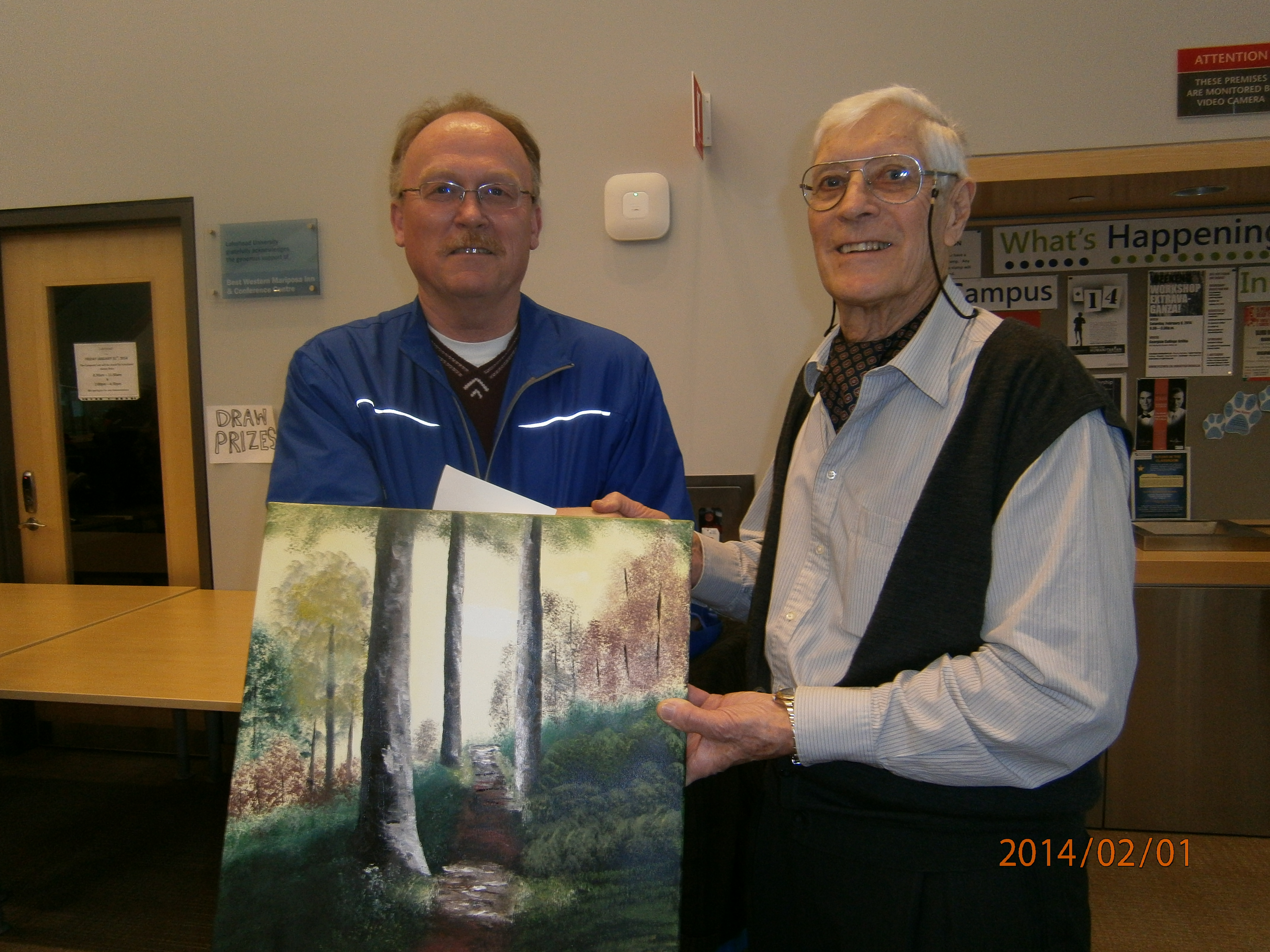 Les Stewart, left, with HWOA chair Bruce Keeling. Stewart won the Meade Helman painting donated by AWARE Simcoe