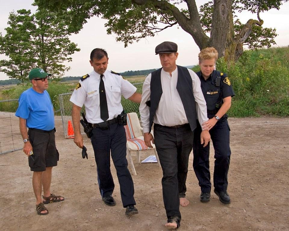 Flashback to 2009: Durham dairy farmer Michael Schmidt is led away from Dump Site 41 -AWARE Simcoe photo