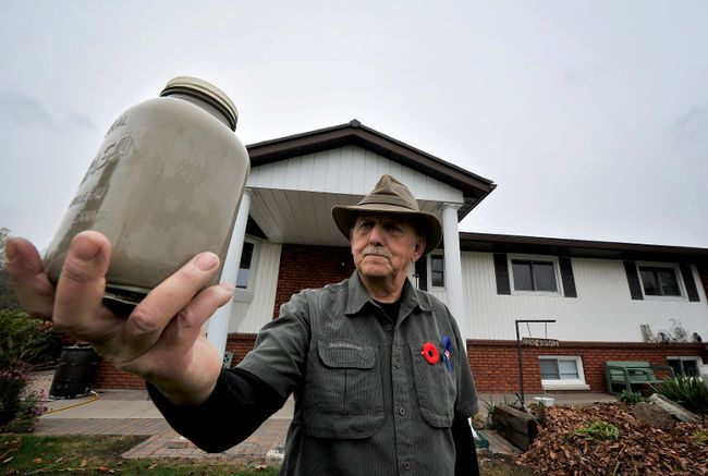 Peter Anderson holds a mason jar of water from his well -Barrie Examiner photo